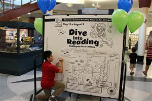 A child signs a giant reading log at the Gail Borden Public Library in Elgin.