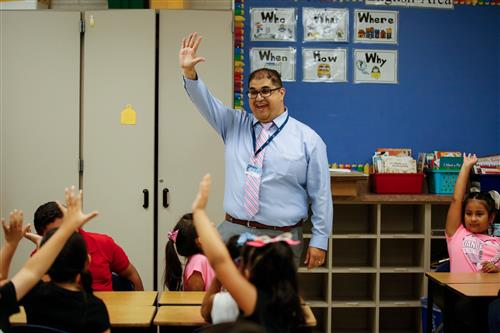 Lords Park Principal Noe Velazquez raises his hand with a group of students