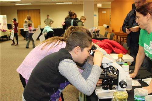 Students look in a microscope at the Bartlett Public Library