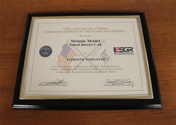 Melanie Meidel receives an award from the Department of Defense