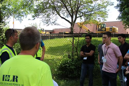 Student interns in front of construction equipment at a school