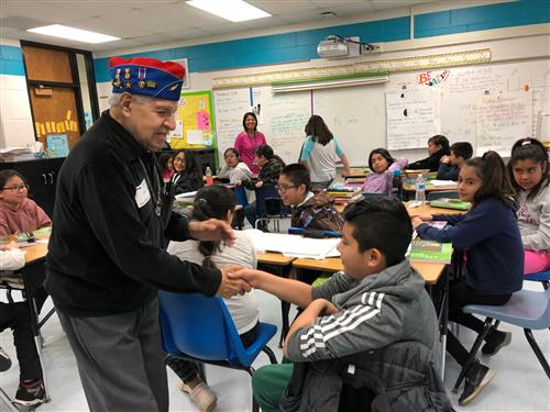 Johnny Vargas shakes a student's hand at Garfield Elementary in Elgin.