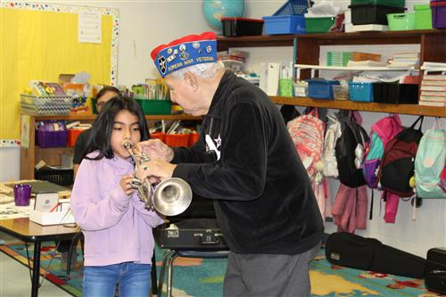 Johnny Vargas shows a student how to play the trumpet.